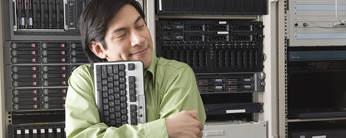 Man Hugging Keyboard infront of Server Rack